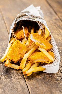 Foto de un fish & chips envuelto en un papel periódico londinense