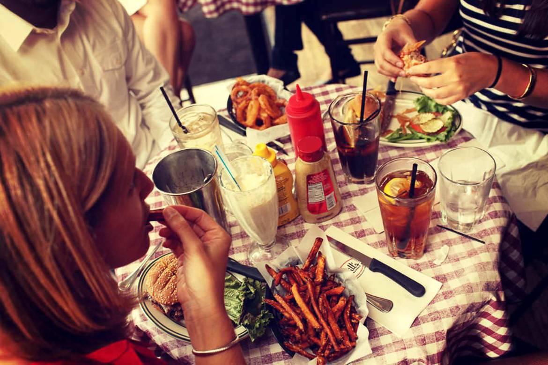 Foto de una cena en Nueva York compuuesta de hamburguesas, patatas y cebolla frita en el Bill's Bar and Burger
