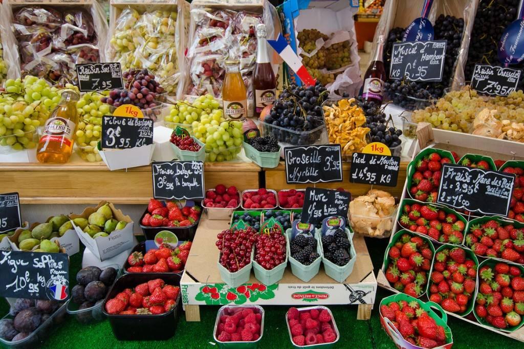 Imagen de un puesto con bayas, uvas, y otros frutos en un mercado francés.