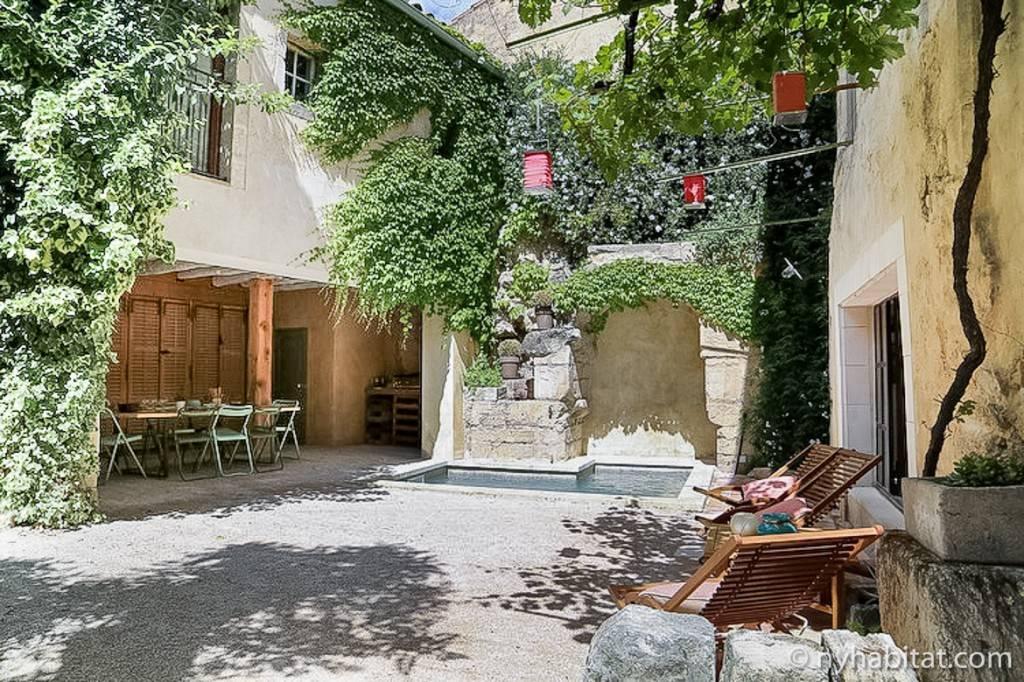 Imagen de una soleada terraza con piscina y sillones de exterior en una villa en Boulbon, cerca de Aviñón.
