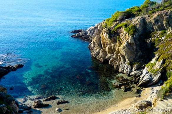 Imagen de una pequeña cala en el mar Mediterráneo con escalones de piedra que llevan a la playa.