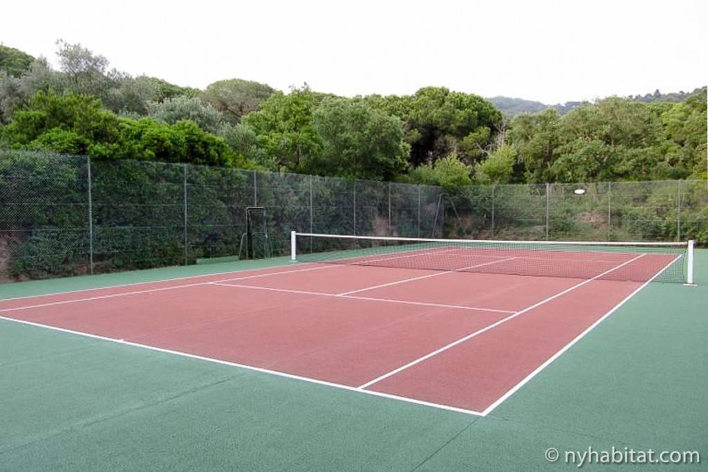 Imagen de una pista de tenis rodeada de vegetación situada en un complejo residencial de lujo.