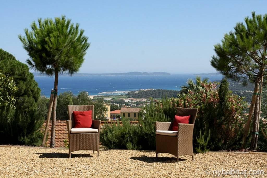 Imagen de dos sillones de exterior en una terraza que mira al mar Mediterráneo.