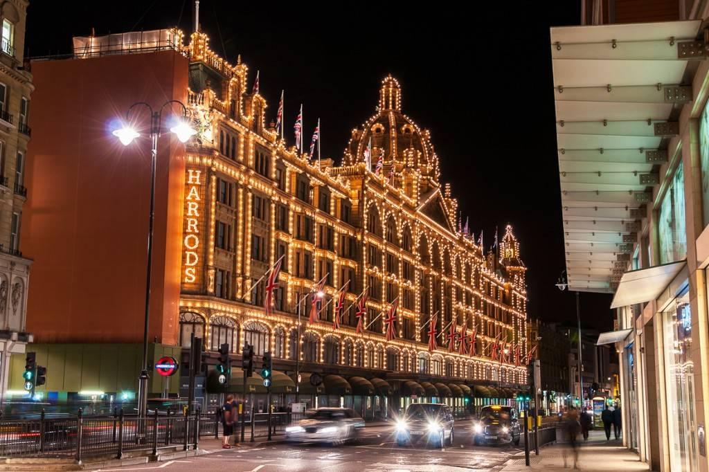 Imagen de los grandes almacenes Harrods frente a una calle con tráfico durante la noche, decorado con luces y adornos navideños
