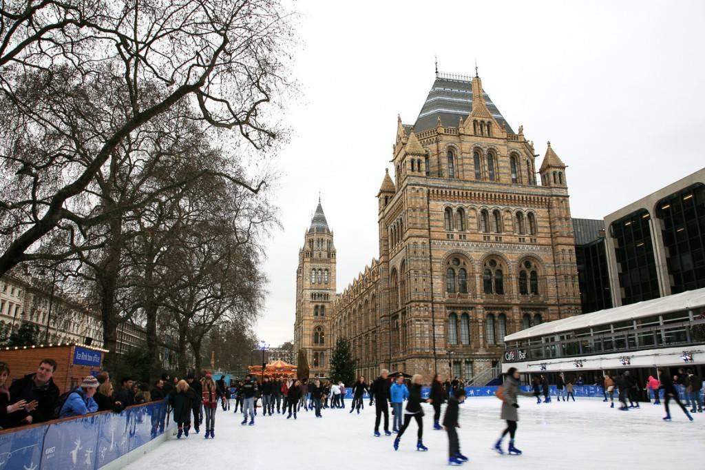 Imagen de un grupo de gente patinando sobre hielo en una pista de patinaje al lado del Museo de Historia Natural de Londres