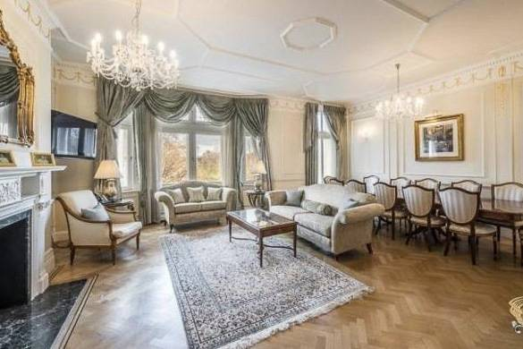 Imagen de una sala de estar acondicionada con sofás, suelos de madera, televisión de pantalla plana a la izquierda, ventanales y una mesa de comedor
