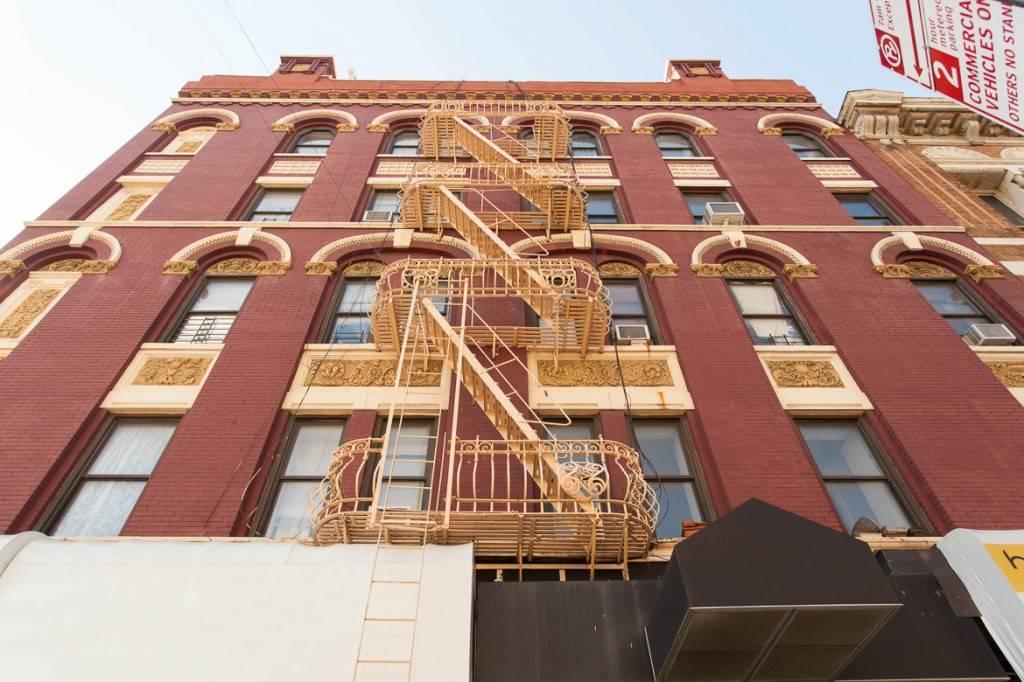 Imagen de un edificio de ladrillo rojo con una salida de incendios de color crema y escalera desplegable