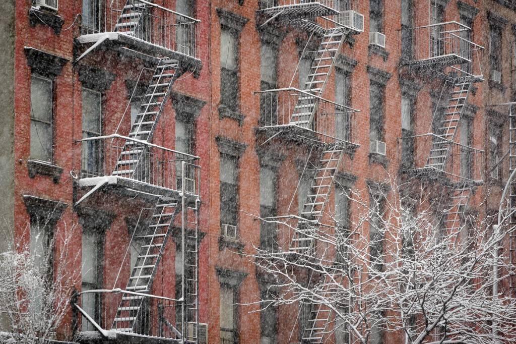Imagen de una hilera de edificios de baja altura en Nueva York con sus salidas de incendios cubiertas por la nieve