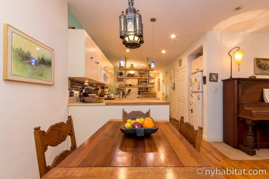Imagen de un apartamento con una mesa de comedor de madera y la cocina blanca.