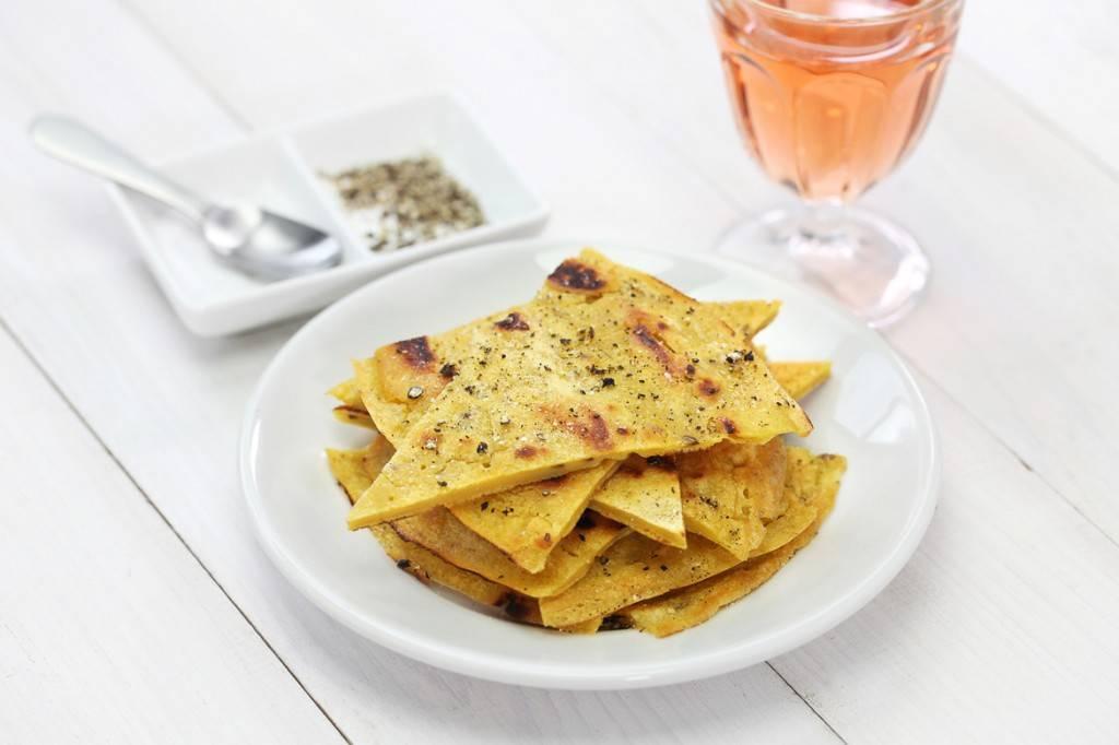 Imagen de un plato con porciones de socca, sal y pimienta, y un una copa de vino rosado.