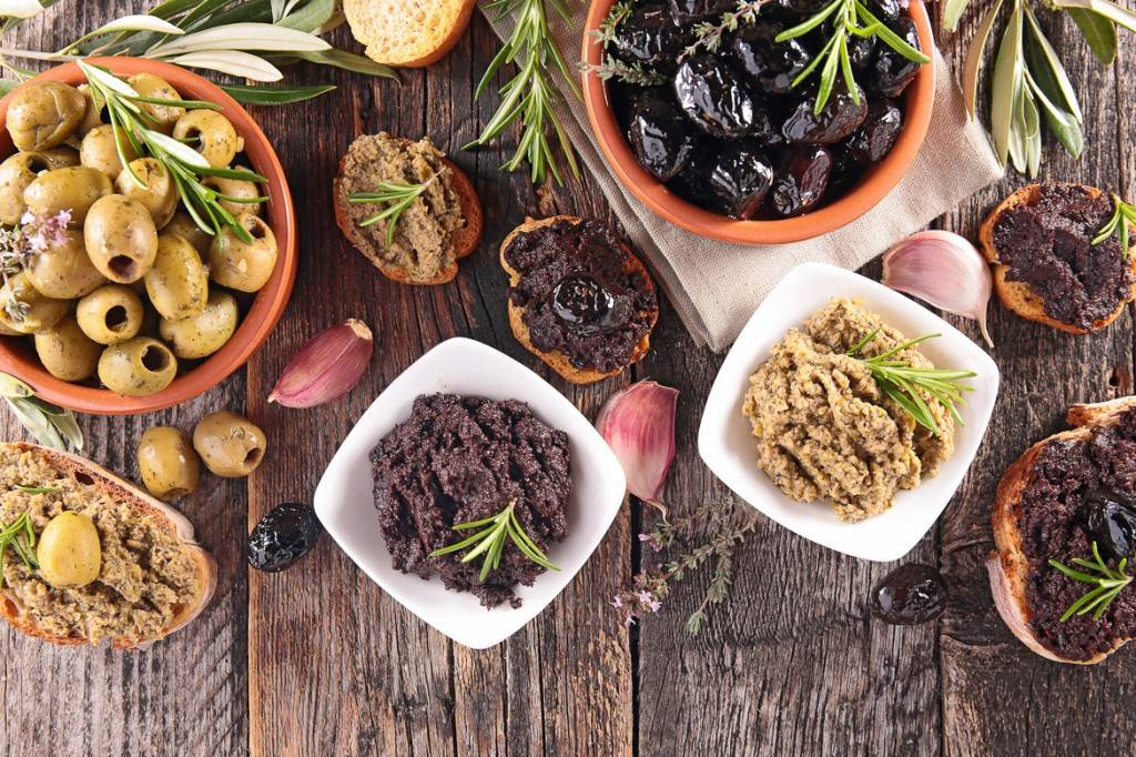 Imagen de una mesa llena de distintos tipos de aceitunas y patés de aceituna.