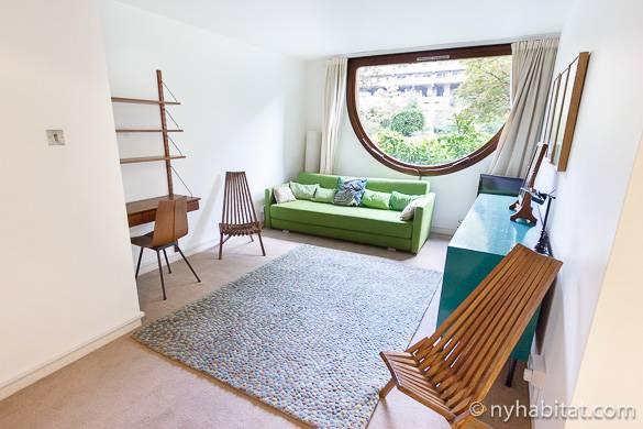 Imagen del salón del apartamento LN-1037 con una ventana tipo barco desde la que se pueden observar los árboles.
