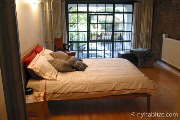 Imagen del salón del apartamento LN-824 con puertas francesas y ladrillo expuesto.