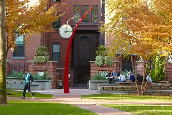 Imagen del campus del Pratt Institute con estudiantes y modernas obras de arte.
