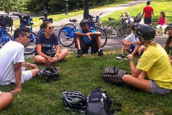 Imagen de personas sentadas en círculo en el parque con bicicletas