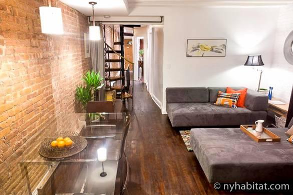 Imagen de la sala del apartamento NY-15192 con sofás, una pared con ladrillo visto y una escalera de caracol.
