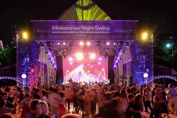 Imagen de personas bailando swing durante la noche con un escenario de fondo