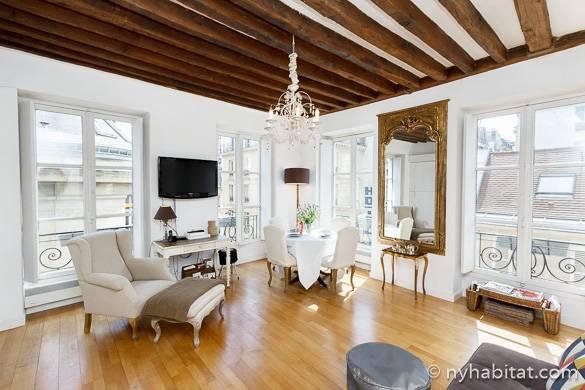 Fotografía del rincón del salón del apartamento PA-3783 con lámpara de araña y techos de vigas vistas de madera