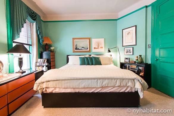 Imagen de la cama en el dormitorio de paredes verdes del apartamento NY-4968