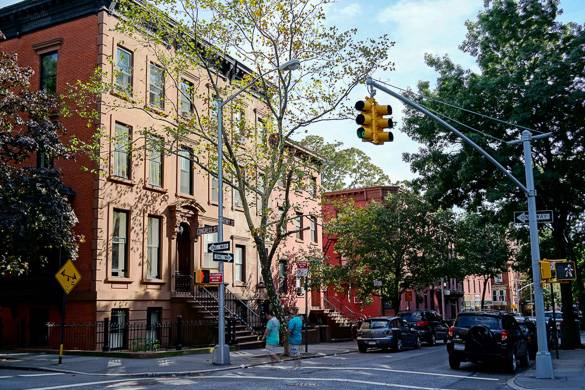 Imagen de edificios de piedra rojiza en la esquina de una calle arbolada