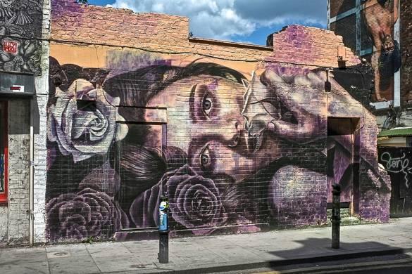Imagen del rostro de una mujer pintado con spray en la parte trasera de un edificio