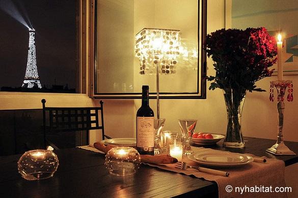 Imagen de una mesa de comedor preparada con vino, flores y velas con la Torre Eiffel iluminada de fondo