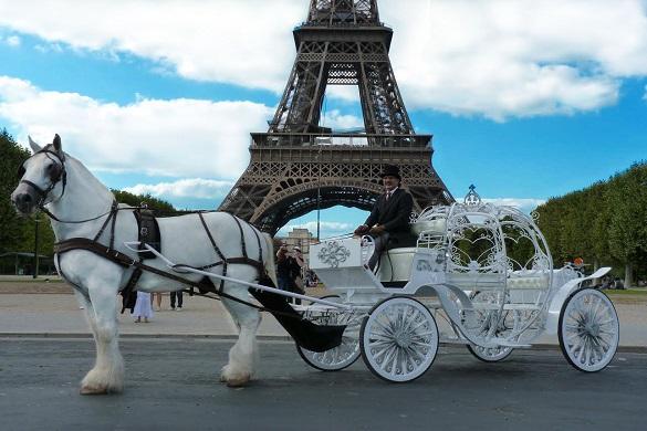 Imagen de un coche de caballos a los pies de la Torre Eiffel