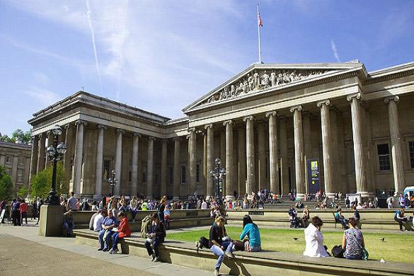 Imagen de gente sentada en los peldaños y en el césped del Museo Británico