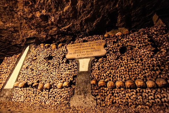 Imagen de calaveras y huesos expuestos artísticamente en las Catacumbas de París.