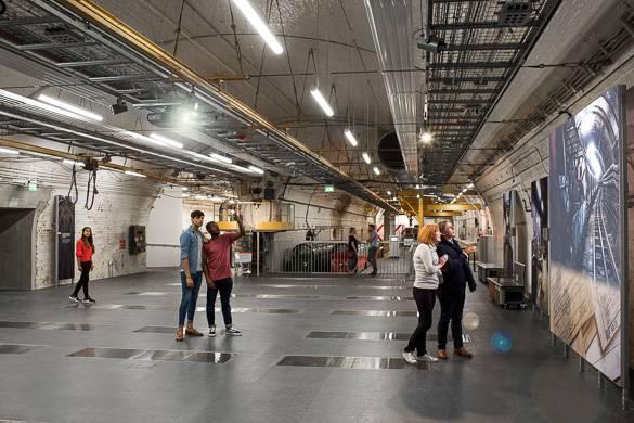 Imagen de personas admirando la obra de arte del depósito de ingeniería de trenes del Museo Postal
