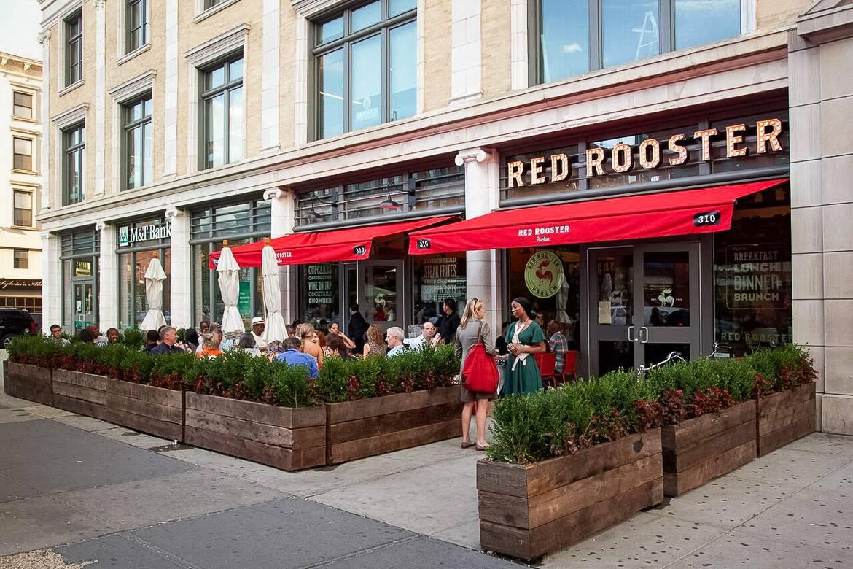 Imagen de la zona exterior con mesas para sentarse de Red Rooster en Harlem