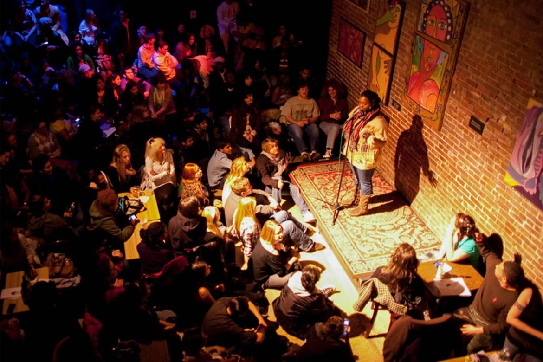 Imagen de una persona en el escenario poco iluminado de un local de poesía