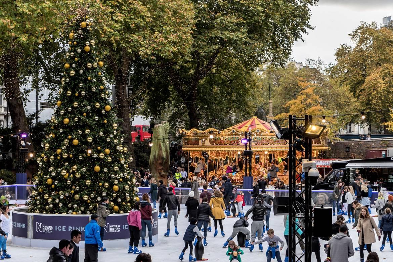 Imagen de una pista de hielo con un árbol de Navidad y un tiovivo