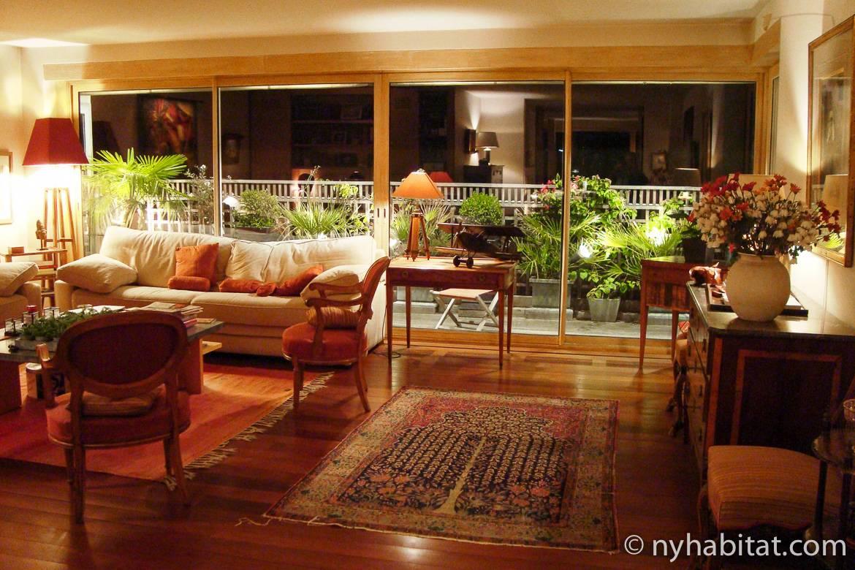 Imagen del salón del apartamento PA-4706 con una pared con ventanales que dan a la terraza con plantas.