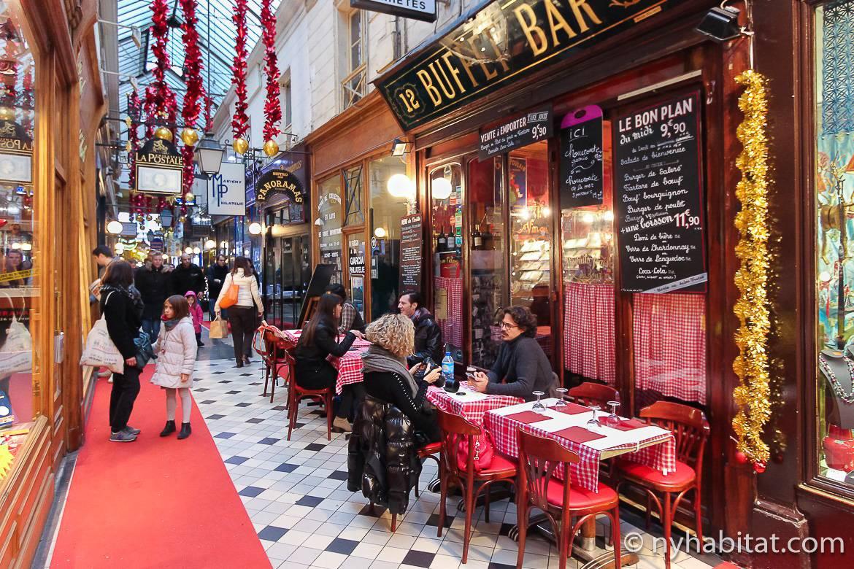 imagen de gente comiendo dentro de la galería comercial Passage du Panorama con techo de cristal y decoración navideña