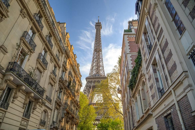 Imagen de la Torre Eiffel con edificios parisinos a los lados.