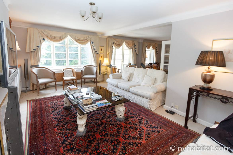 Imagen de la sala de estar de LN-1484 con alfombra roja, mesa de centro, sofá y 3 ventanas grandes