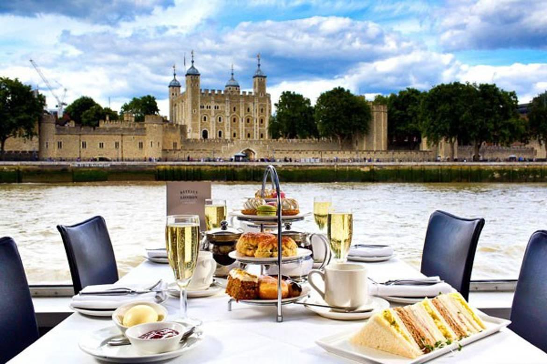 Imagen de tazas de té, copas de champán, sándwiches y bizcochos servidos en una bandeja de tres alturas y con vistas al río en el fondo