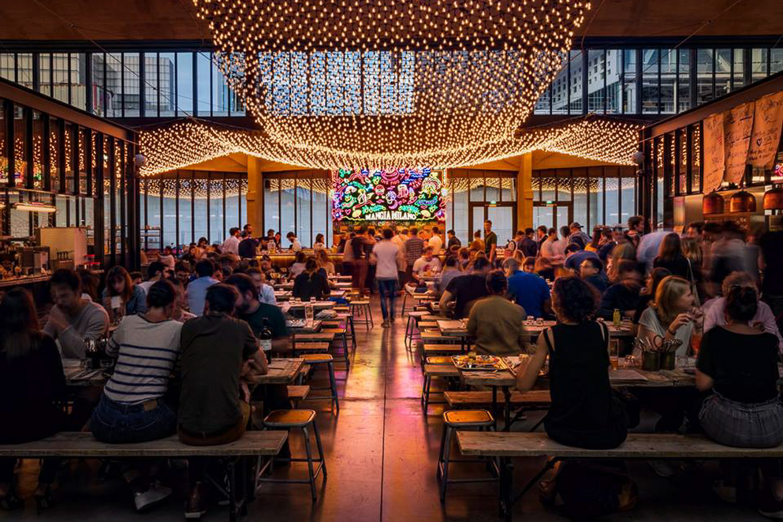 Imagen de personas cenando bajo un techo de luces festivas en La Felicitá