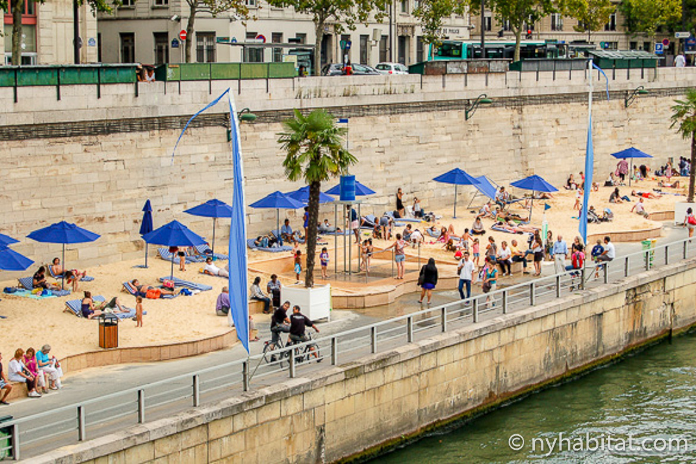Imagen de personas relajándose en las Paris Plages junto al Sena con sombrillas azules.