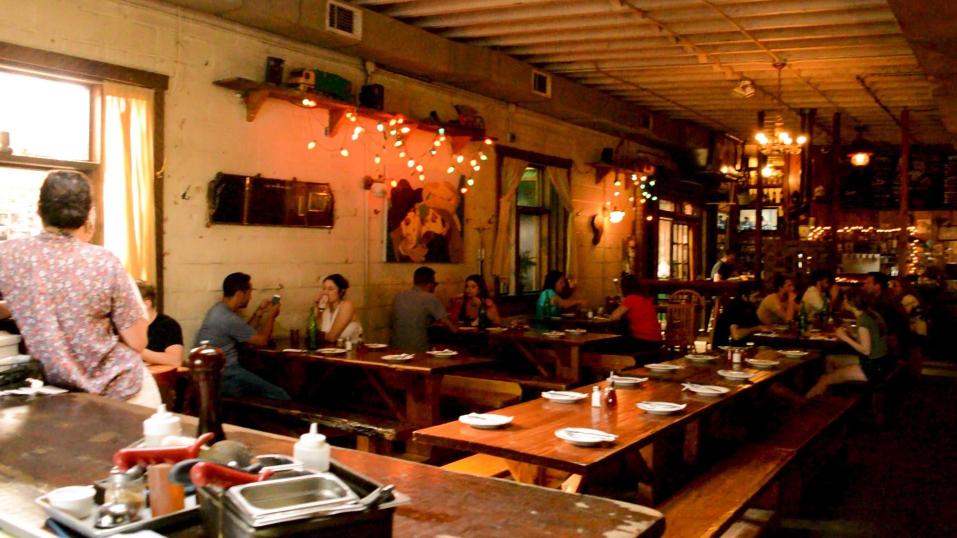 Imagen de jóvenes disfrutando de comida y bebida en un bar en Bushwick, Brooklyn.