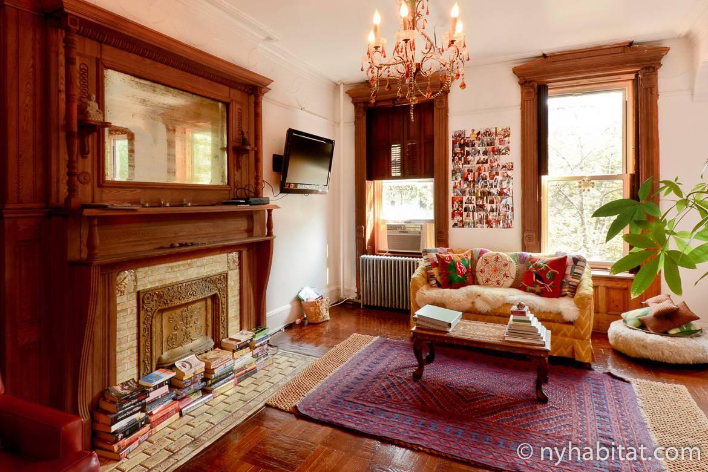 Imagen del salón del NY-14321 con una chimenea y un sofá con cojines decorativos.