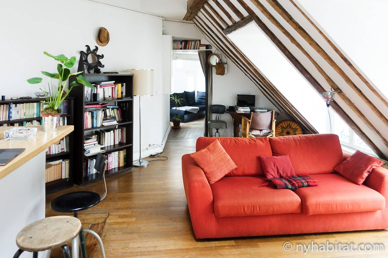 Imagen de una sala de estar en PA-3780 con un sofá rojo, estanterías y techos de vigas vistas.