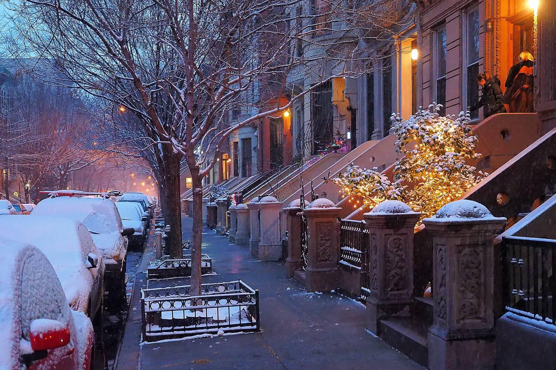 Imagen de una calle residencial de Nueva York con edificios de piedra rojiza tras una nevada