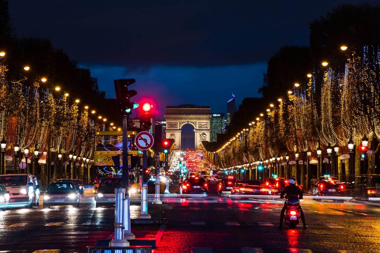Imagen de los Campos Elíseos de París con luces de Navidad en los árboles.