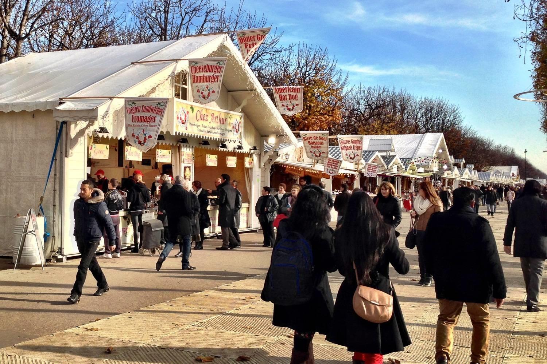 Imagen de mercado de Navidad a lo largo de los Campos Elíseos con puestos de comida y tiendas.