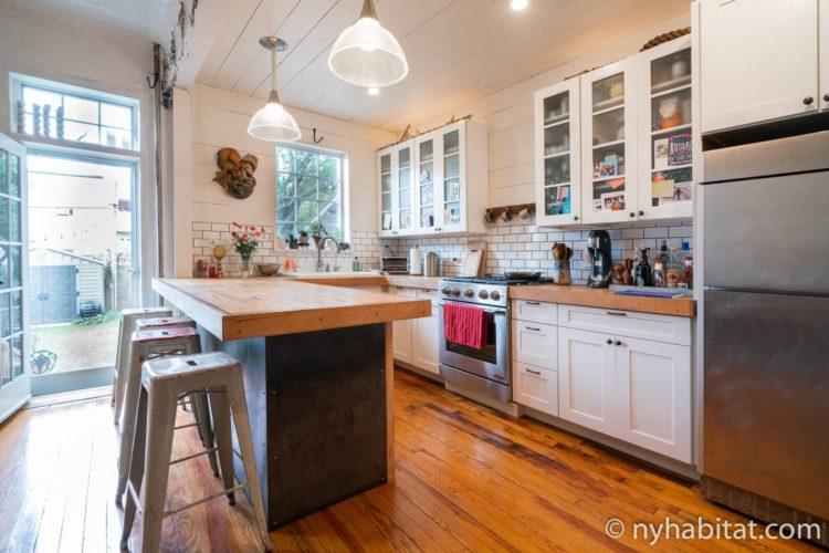 Imagen de una cocina en NY-17687 con electrodomésticos y taburetes.