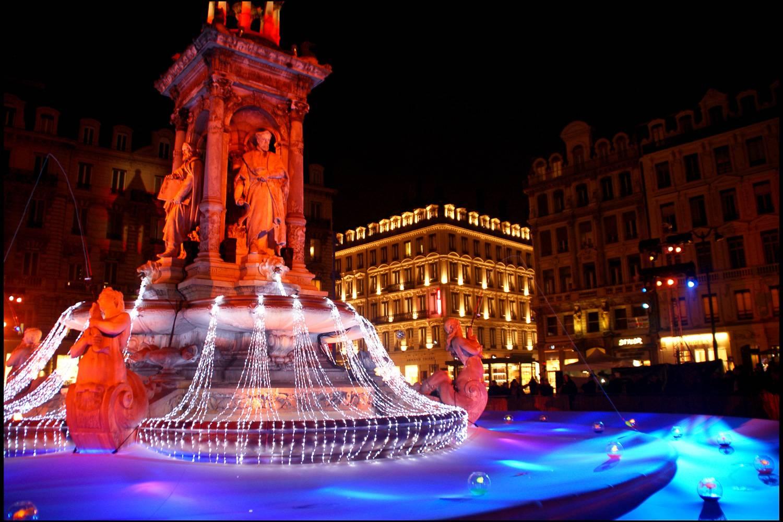 Imagen de una fuente en Lyon decorada con luces para la Fête des lumières.