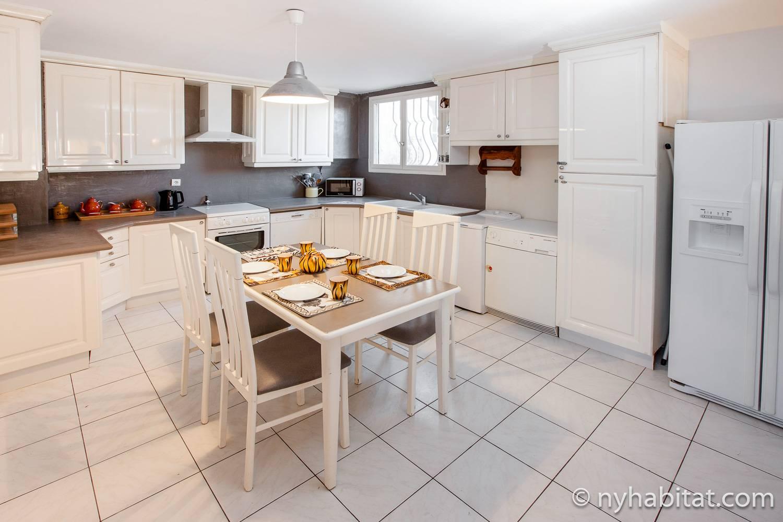 Imagen de la cocina en PR-1170 con mesa de comedor y encimeras blancas.