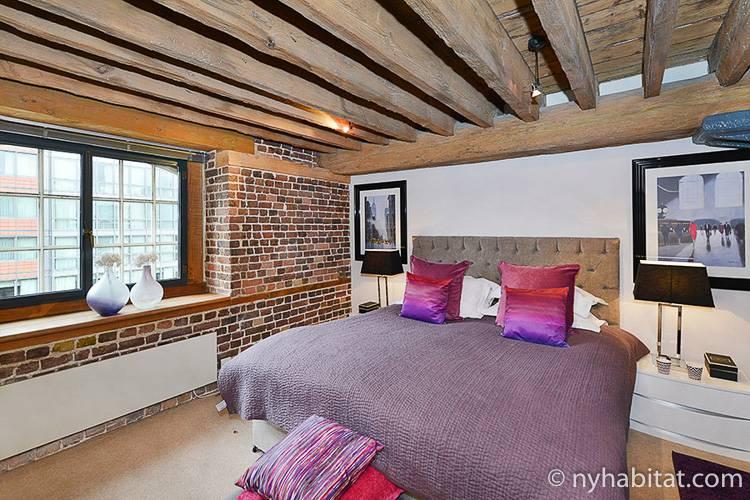 Imagen del dormitorio del LN-1581 con cama de matrimonio, mesita y adornos.